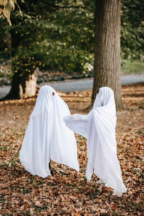 Full body playful kids in white ghost costumes having fun on Halloween in park