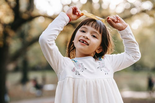 Happy playful child holding fallen leaves while spending time in garden and looking at camera