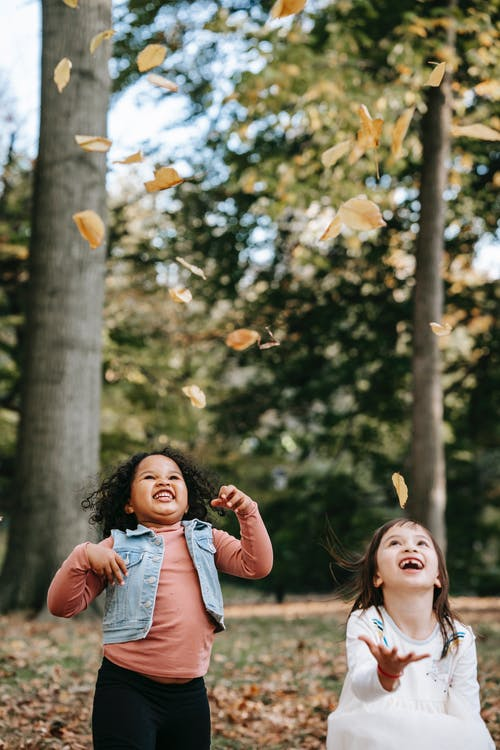Happy multiracial girls having fun while playing with fallen leaves in autumn park