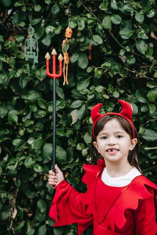 Little girl in devil costume near shrub