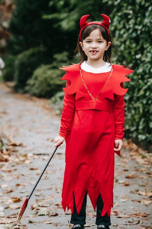 Cheerful child in devil costume on Halloween