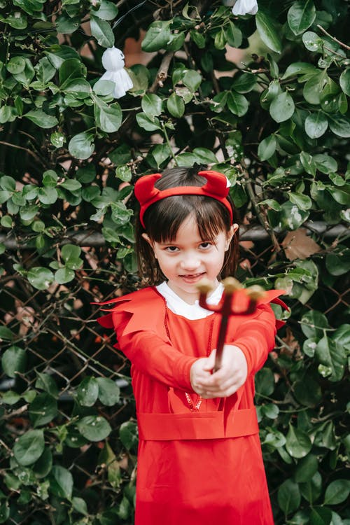 Adorable preschool girl in headband with devil horns standing near bush and pointing at camera with trident