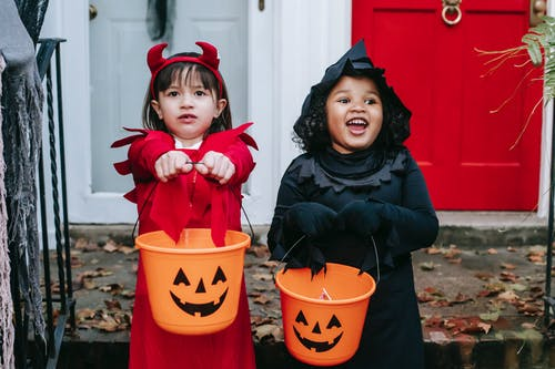 Funny multiethnic girls with buckets on Halloween