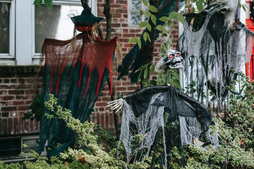 Spooky skeleton and witches on wooden sticks near entrance of brick house on Halloween