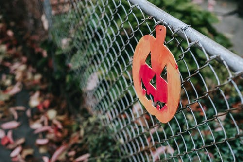 High angle of painted decorative pumpkin on metallic lattice fence on Halloween holidays