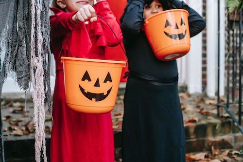 Crop children with buckets on Halloween