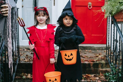 Diverse preschool girlfriends in costumes holding buckets and trident while standing near door on Halloween