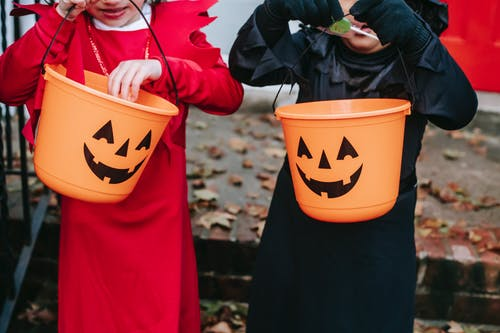 Crop kids with Halloween buckets for candies