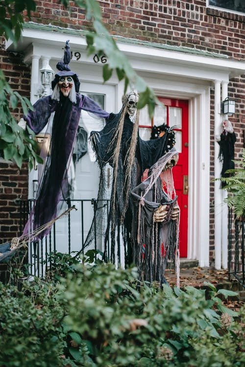 Terrible scarecrows of witch and skeletons on fence near entrance of brick building