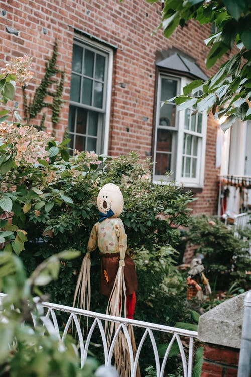 Scarecrow between bushes behind iron fence