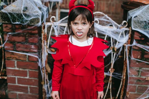 High angle of preschool girl with fangs in devil costume standing near fence with cobweb and intimidating looking at camera