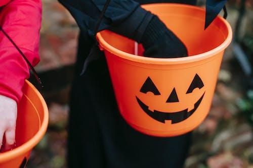 Crop kids folding treats in bucket on Halloween