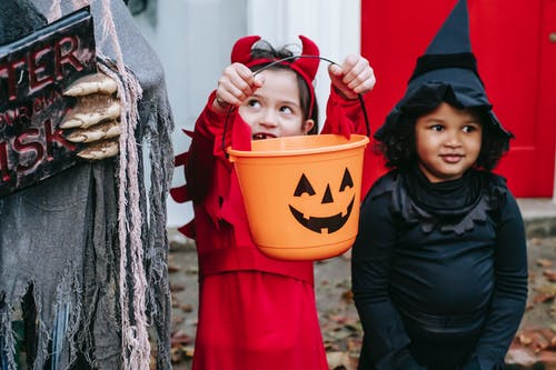 Multiracial kids in Halloween costumes near decorations