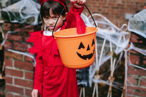 Frightening preschool girl in costume reaching hand with bucket for candies and looking at camera