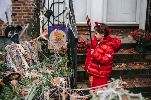 Little girl in devil costume on Halloween near house