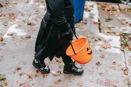 Crop unrecognizable child in black witch costume strolling with bucket on Halloween in autumn day on street