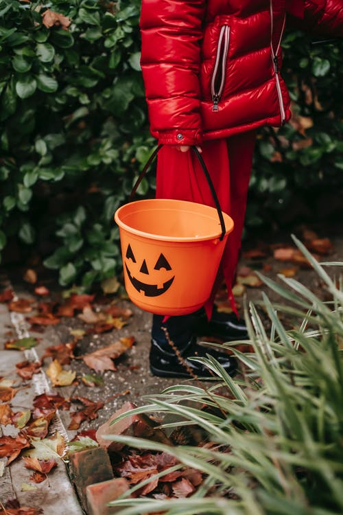 Faceless kid in costume on Halloween with bucket