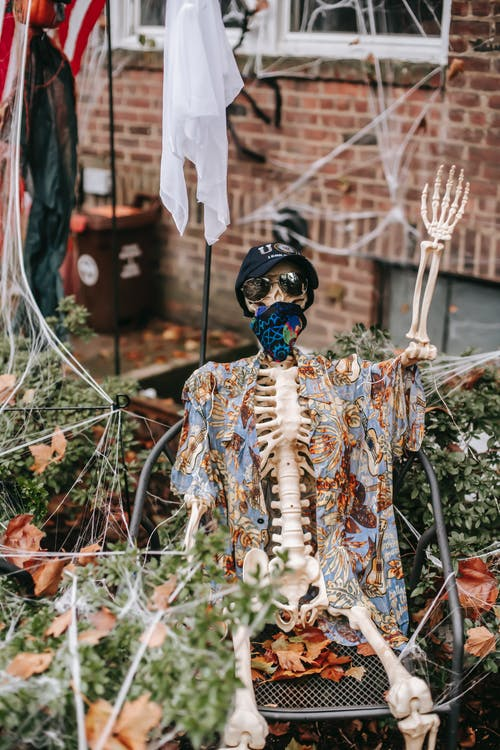 Skeleton sitting near house in Halloween day