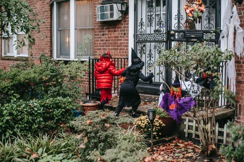 Unrecognizable little girls in costume trick or treating on Halloween