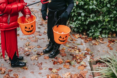 Crop unrecognizable kids in red devil costume with pitchfork and in black witch costume on Halloween with buckets full of candies standing on road in autumn day