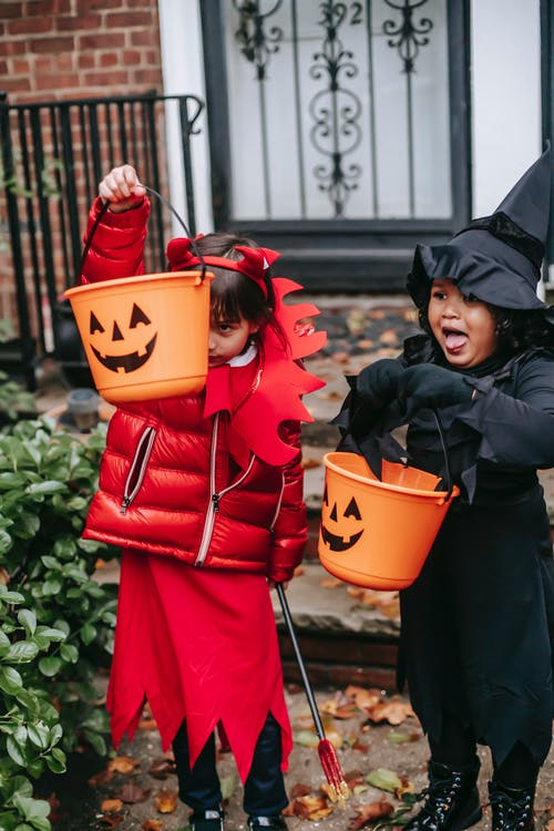 Little girls in red devil costume with horns and pitchfork and in black witch costume with hat with orange buckets on Halloween standing near house door in autumn