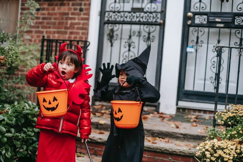Funny children in witch and devil costumes carrying buckets for candies and showing creepy grimaces against house in neighbourhood