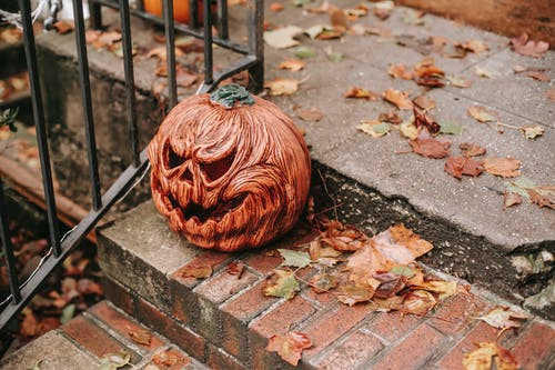 Carved pumpkin placed on stairs on Halloween