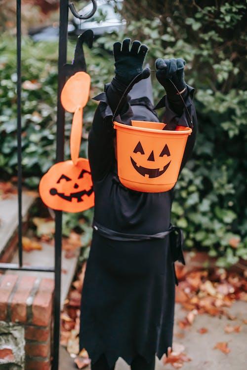 Little kid in Halloween black costume standing in garden with orange bucket