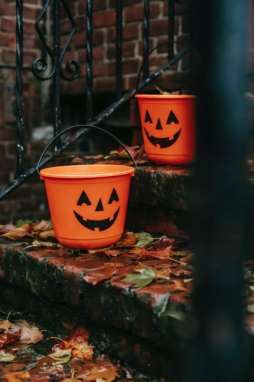 Orange buckets with Halloween symbols outside house