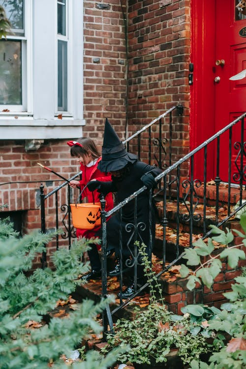 Kids in Halloween costumes with orange buckets going down on front steps of red brick house