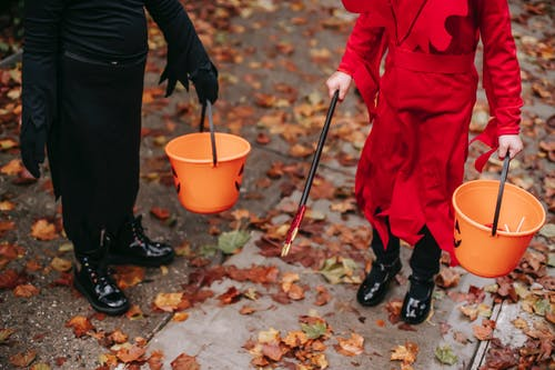 Kids walking on street with buckets on Halloween