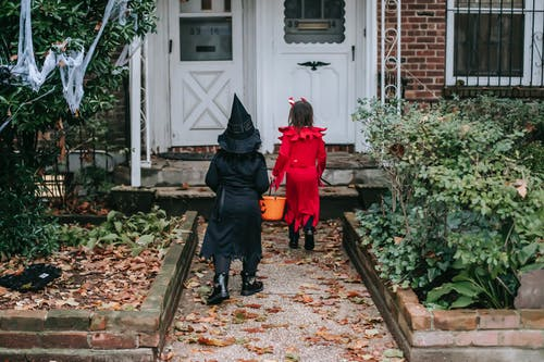 Back view of little children in traditional Halloween costumes going to front doors of semi detached red brick house playing trick or treat custom