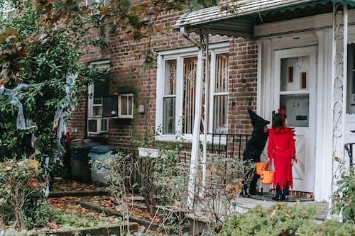 Little kids in fancy Halloween costumes outside house