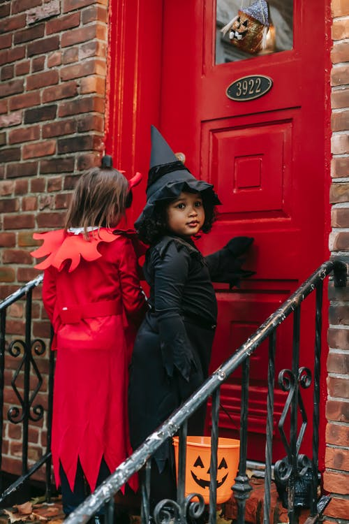 Spooky girl wearing with bucket witch costume and unrecognizable kid in devil wear standing on porch near entrance of house while playing trick or treat game