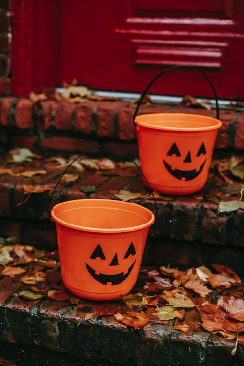 Jack O Lantern Halloween candy bucket placed on wet doorstep with fallen leaves near entrance of building during holiday celebration