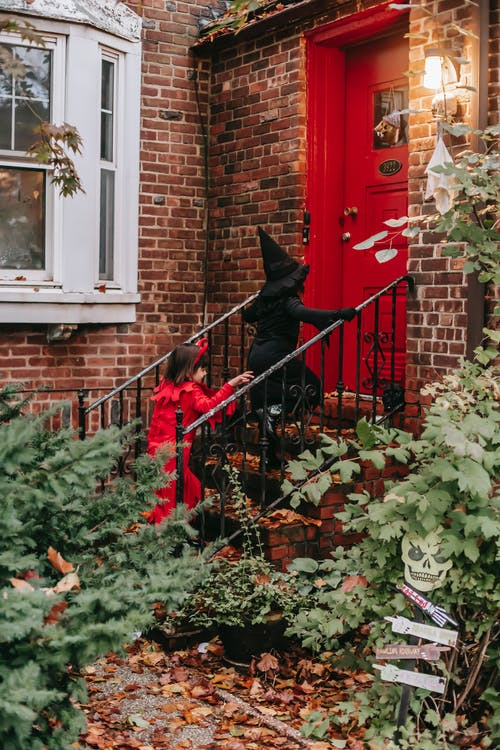 Side view of anonymous children wearing witch and devil costumes walking upstairs at entrance of brick house while celebrating holiday
