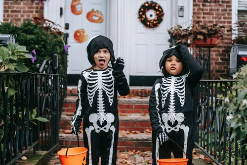 Multiracial children trick or treating in skeleton costumes on Halloween