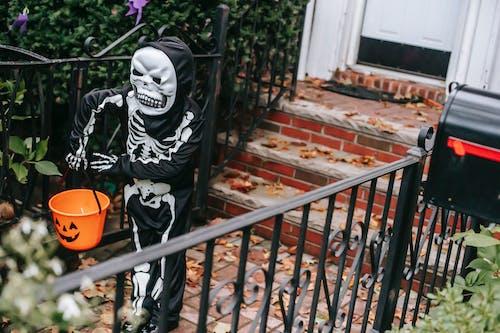 Full body of faceless kid in skeleton costume with orange bucket and mask walking near house door in Halloween