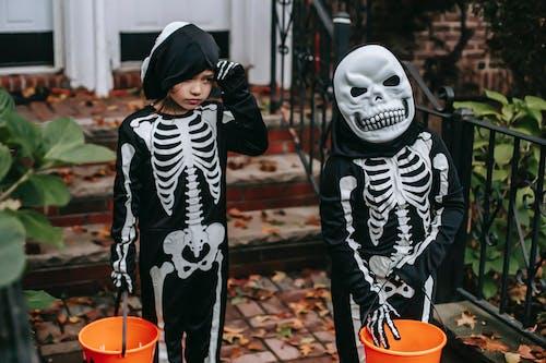 Children in skeleton costumes trick or treating in Halloween