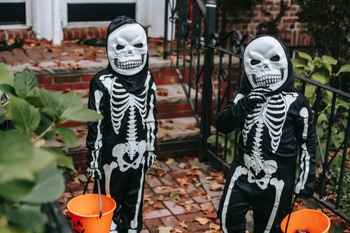 Unrecognizable kids in Halloween costumes standing near house