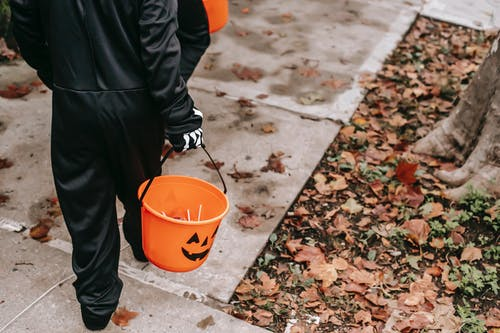 Crop faceless kids in black Halloween costumes with orange buckets filled with candies strolling on sidewalk in daytime