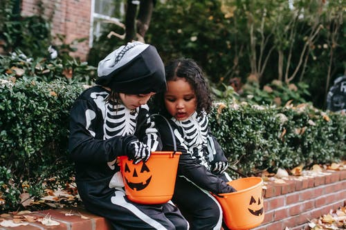 Multiethnic girls in Halloween costumes with buckets of candies on street