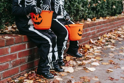 Children in Halloween costumes resting on fence with jack o lantern buckets