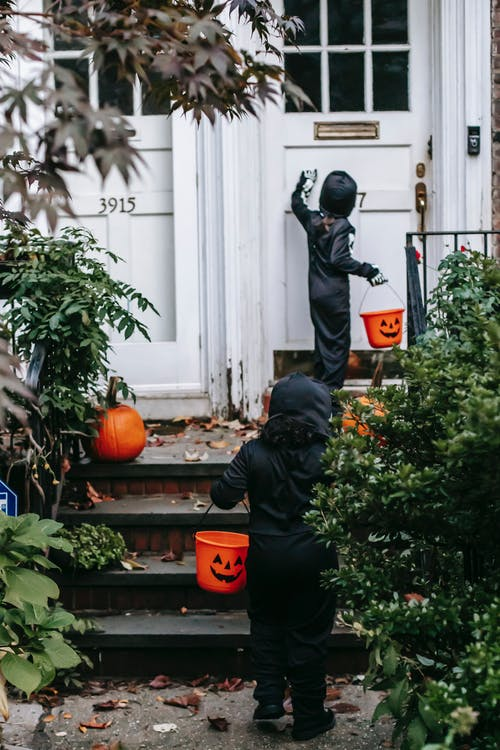 Unrecognizable children dressed in black Halloween costumes trick or treating