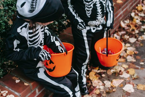 From above of crop faceless child standing near girl wearing skeleton costumes preparing to trick or treat with candy buckets during Halloween celebration