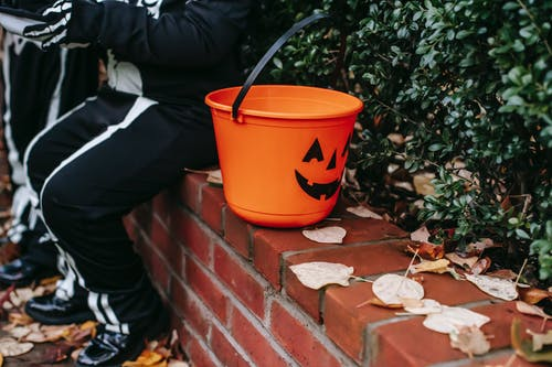 Crop child sitting with plastic bucket decorated as jack o lantern