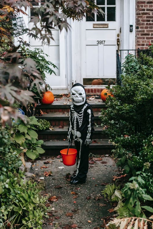 Unrecognizable kid wearing Halloween skeleton costume and scary mask standing with orange bucket near staircase of house decorated with pumpkins and looking at camera