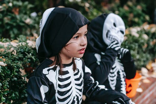 Cute little preschool girl sitting near garden with friend wearing scary costume