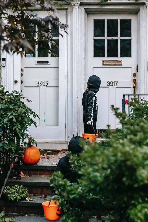 Back view of crop unrecognizable child in skeleton costume knocking on door for trick or treat while another child with bucket standing behind
