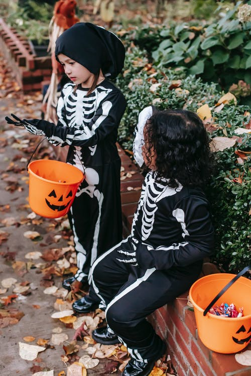 Cute little children resting after trick or treat during Halloween celebration